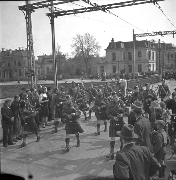 Pipe band of The Essex Scottish Regiment marching across a bridge which had been captured by the regiment, Groningen, Netherlands, 17 April 1945.