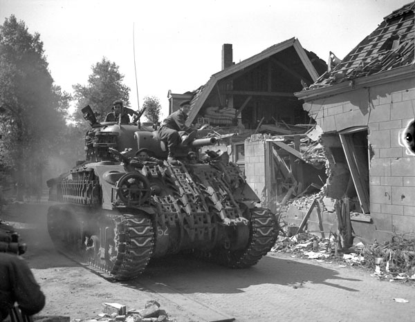 A Sherman Vc Firefly tank of the 8th Princess Louise's (New Brunswick) Hussars en route to the Zuider Zee passing through Putten, Netherlands, 18 April 1945.