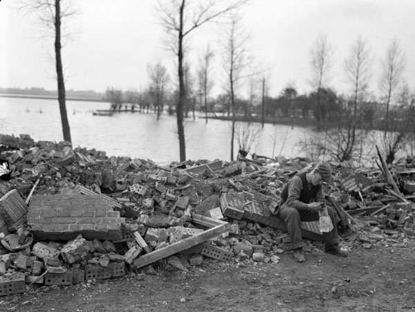 Sapper M.J. Barratt of the Royal Canadian Engineers (R.C.E.), 3rd Canadian Infantry Division, amid rubble at the east end of the Leopold Canal, Netherlands, 16 October 1944.