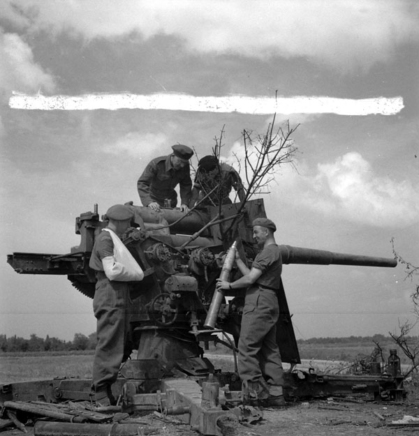 Canadian Film and Photo Unit personnel with a captured German 88mm anti-aircraft gun near Bayeux, France, 26 August 1944.