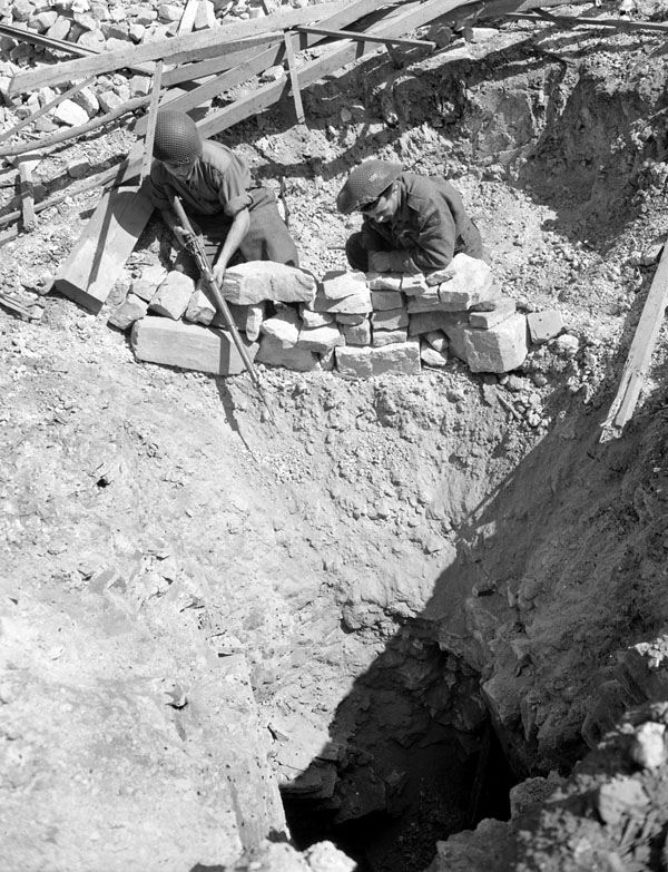 Les Fusiliers de Mont Royal looking into mine shaft used by German troops for infiltration purposes, between Saint-André-sur-Orne and May-sur-Orne, France, 9 August 1944.