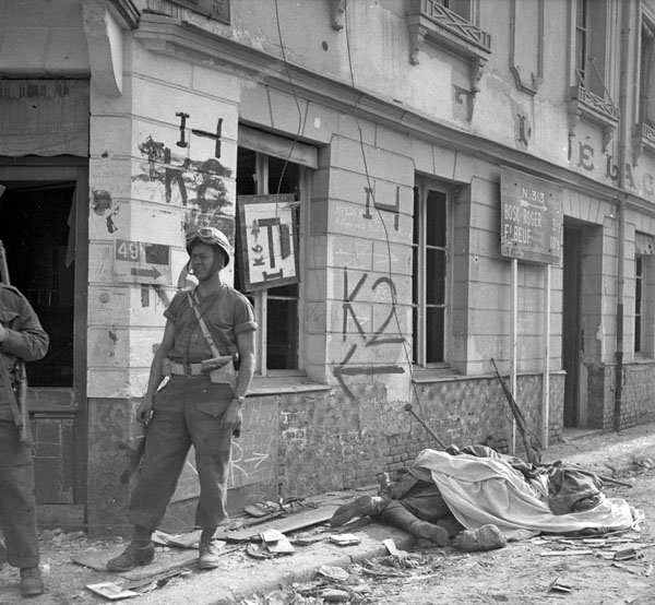 Lance-Corporal W.H. Harris of the Canadian Provost Corps (C.P.C.) on guard near bodies of German soldiers, Bourgtheroulde, France, 27 August 1944.