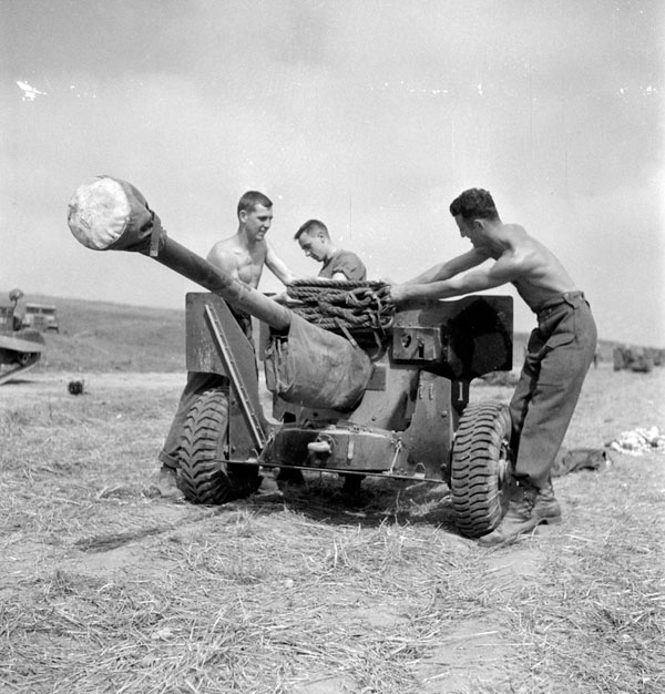 Infantrymen of The Highland Light Infantry of Canada attaching drag ropes to a six-pounder anti-tank gun, Thaon, France, 6 August 1944.