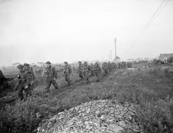 Canadian infantrymen advancing at dawn during Operation SPRING south of Vaucelles, France, 25 July 1944.