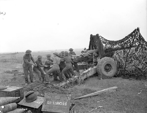 Gunners of a Medium Regiment of the Royal Canadian Artillery (R.C.A.) cleaning a 5.5-inch gun south of Vaucelles, France, 23 July 1944.