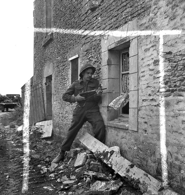 A Royal Canadian Engineer (R.C.E.) Sapper armed with a Sten gun, searching buildings for enemy snipers, Gruchy, France, 9 July 1944.