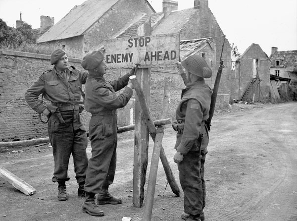 Stop, Enemy Ahead sign being erected by personnel of No. 4 Provost Company, Bretteville-le-Rabet, France, 23 June 1944.