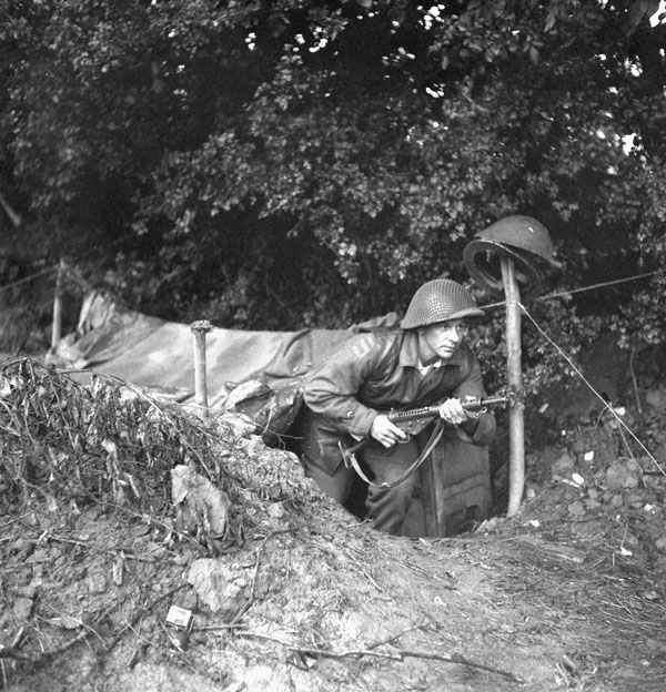 Sapper Joe Iaci, 6th Field Company, Royal Canadian Engineers (R.C.E.) coming out of his dugout, Normandy, France,  3 July 1944.