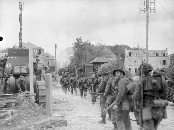 Infantrymen of Le Régiment de la Chaudière moving through Bernières-sur-Mer, France, 6 June 1944.