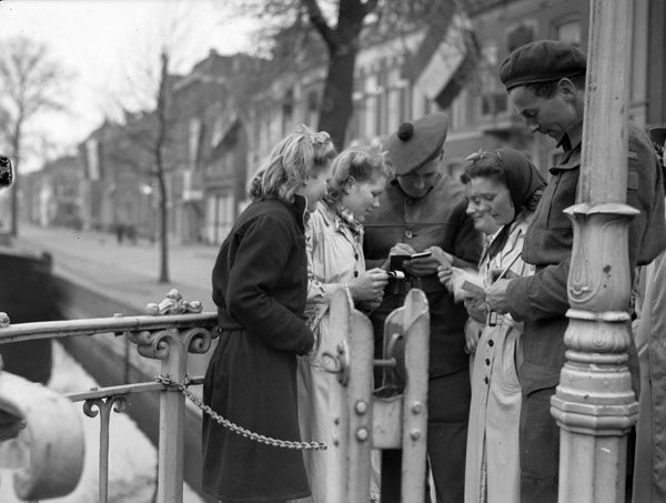 Private J.L. Davies of  The Lorne Scots (Peel, Dufferin and Halton Regiment) (centre) and Private W. Mahar of 9th Canadian Infantry Brigade Headquarters signing autographs, Leeuwarden, Netherlands, 16 April 1945.