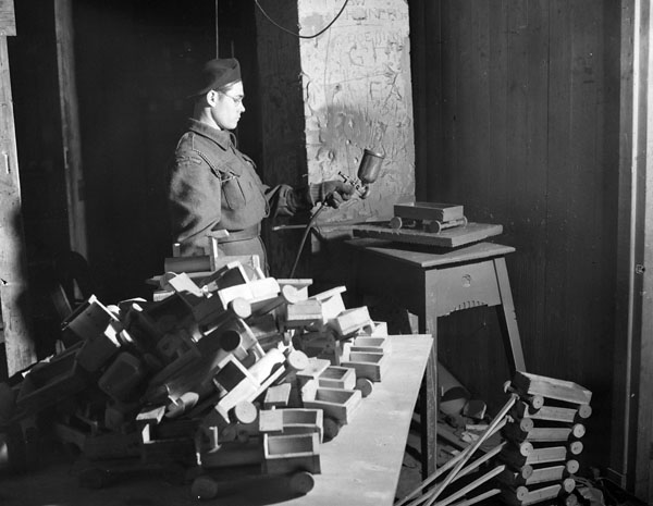 Trooper L.R. Stoutenberg of The Fort Garry Horse painting toys which will be given to children on St. Nicholas Day. Doetinchem, Netherlands, 22 November 1945.