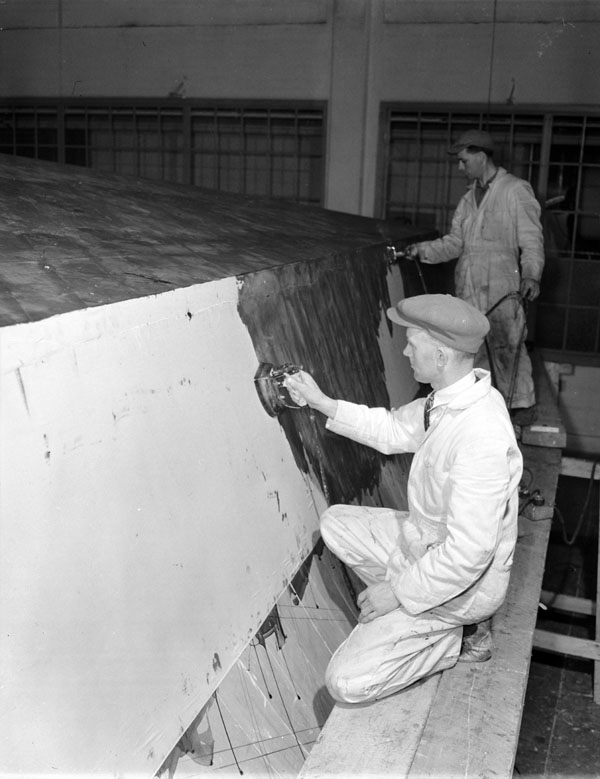 Workers ironing linen fabric onto the hull of a motor torpedo boat under construction at Canadian Power Boat Company, Montreal Québec, Canada, 24 April 1941.