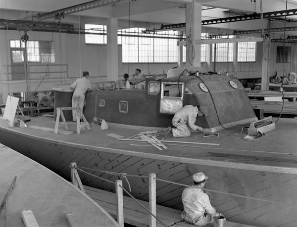 Workers attaching the superstructure to a motor torpedo boat under construction at Canadian Power Boat Company, Montreal, Québec, Canada, 24 April 1941.