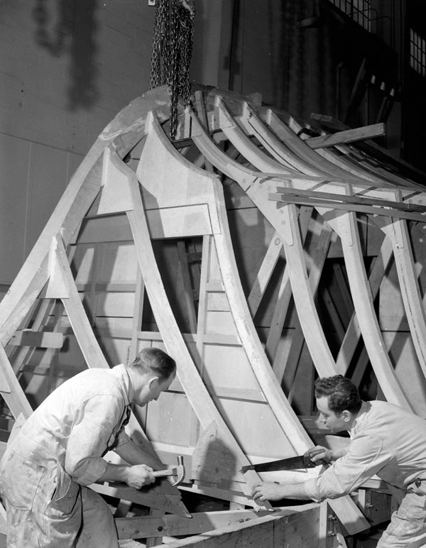 Workers notching a frame of a motor torpedo boat under construction at Canadian Power Boat Company, Montreal, Québec, Canada, 24 April 1941.