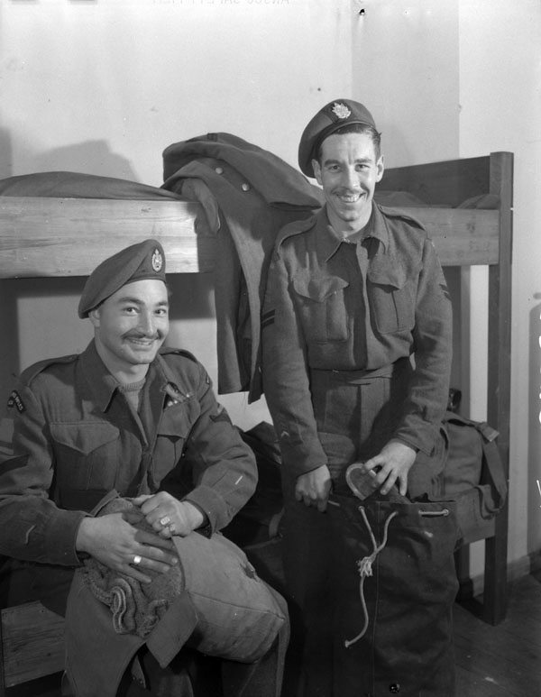Lance-Corporal J.D. Chupa and Corporal J.A. Andrews, both of The Queen's Own Rifles of Canada,  packing their kitbags inpreparation for thirty-day rotation leave in Canada. Rastede, Germany, 31 October 1945.