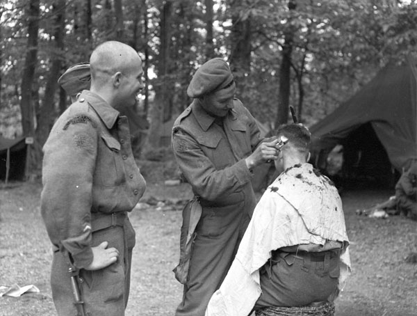 Infantrymen of The Royal Winnipeg Rifles getting haircuts while preparing to embark for the invasion of France. England, 1 June 1944.