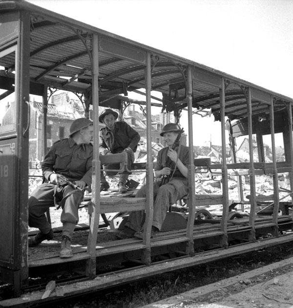 Unidentified infantrymen resting in a damaged streetcar, Vaucelles, France, 18 July 1944.