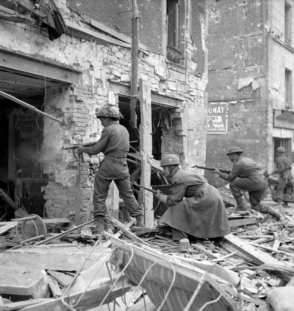 Infantrymen of The Regina Rifle Regiment and a despatch rider firing into a damaged building, Caen, France, 10 July 1944.