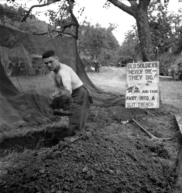 Sergeant  Reg Hannigan of the Royal Canadian Engineers (R.C.E.) digging a slit trench during Operation SPRING south of Ifs, France, 25 July 1944.