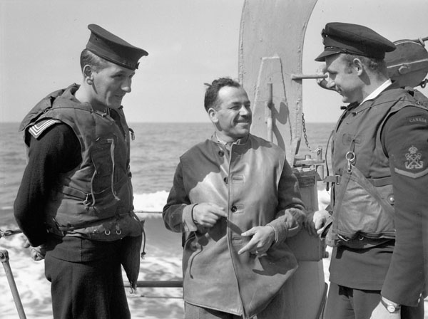 Lieutenant Michael M. Dean (centre) of the Canadian Army Film and Photo Unit with personnel of the destroyer H.M.C.S. ALGONQUIN, which is transporting the staff of 1st Canadian Army Headquarters to France, 18 June 1944.