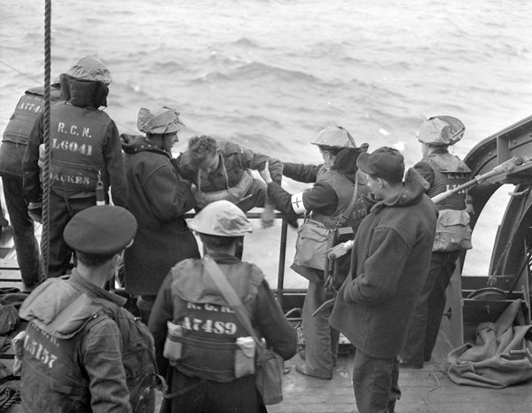 Survivors of a capsized Landing Craft Infantry (LCI) being helped aboard H.M.C.S. PRINCE HENRY off the Normandy beachhead, France, 6 June 1944.