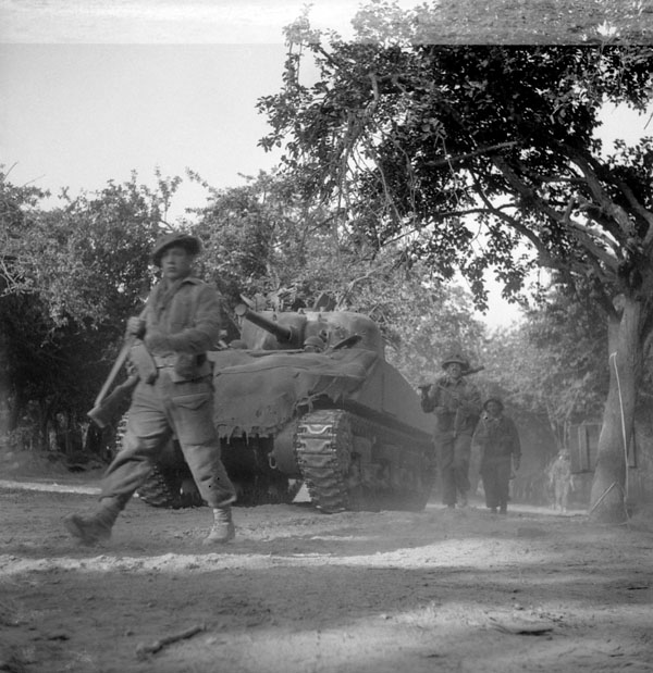 Infantrymen of The Highland Light Infantry of Canada passing Sherman tanks en route to cross the Orne River near Caen, France, 18 July 1944.