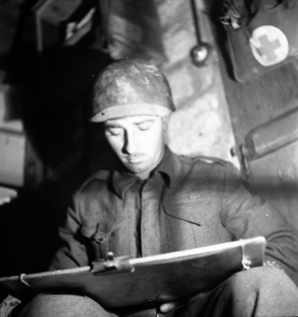 Sergeant-Major Jimmie Young of the Royal Canadian Artillery (R.C.A.) in an underground command post during Operation SPRING south of Fleury-sur-Orne, France, 25 July 1944.