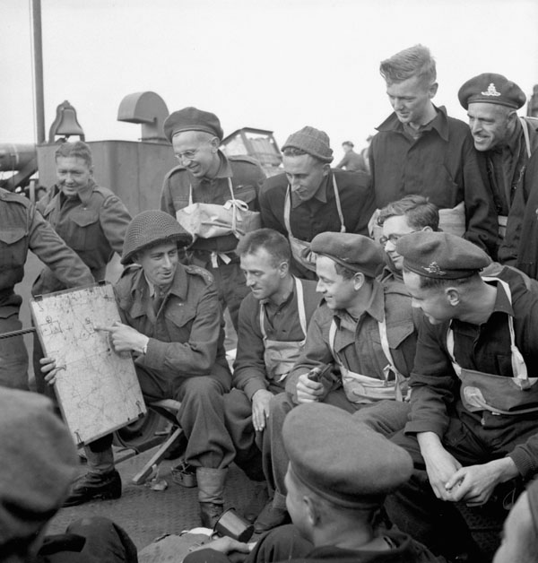 Captain S. Mendelsohn of the Royal Canadian Artillery (R.C.A.) briefing Canadian soldiers aboard a Landing Ship Tank (LST) en route to the Normandy beachhead, France, June 1944.