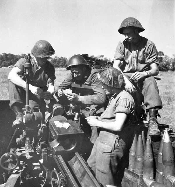 Gunners Len Forbes, Herb Guard, Donald Germscheid and Frank Curliss, all of the 13th Field Regiment, Royal Canadian Artillery (R.C.A.), playing cards as they await firing orders, France, 25 June 1944.
