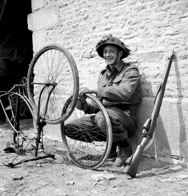 Private R.O. Potter of The Highland Light Infantry of Canada repairing his bicycle, France, 20 June 1944.