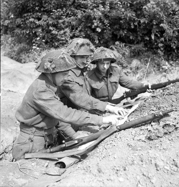 Platoon commander Lieutenant J.H. Chrystler (centre) issuing patrol instructions to Sergeant F.C. Edminston and Private L.J.L. Coté, all of The Highland Light Infantry of Canada, France, 20 June 1944.