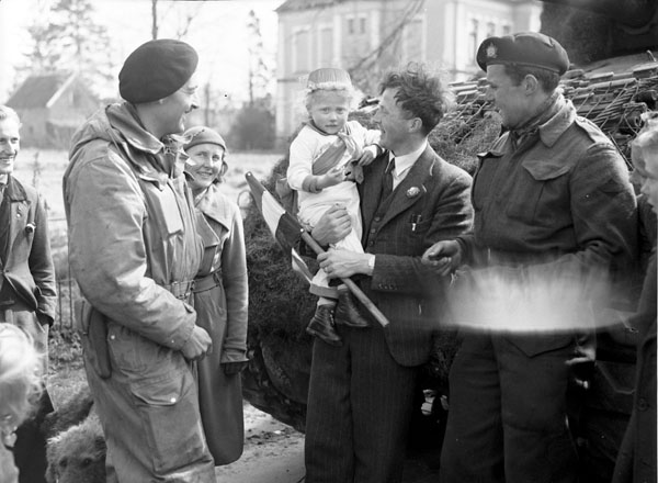 Lieutenant W.J. Trump and Trooper W.H.G. Ritchie of The Fort Garry Horse offering chewing gum to a Dutch child after the liberation of Rijssen, Netherlands, 9 April 1945.