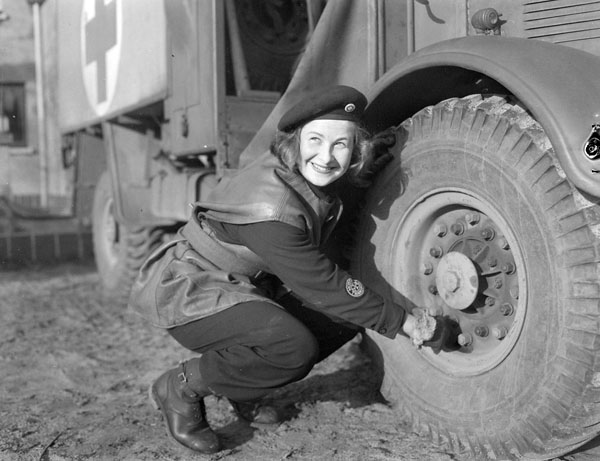 St. John's Ambulance driver Salley MacKean checking tire pressure on her ambulance, De Haan, Belgium, 4 February 1945.