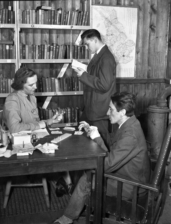 Mrs. Freda Cooper of the Canadian Red Cross playing cribbage with Private W.J. Downey while Private J.C. Veilleux browses in the library of No.18 Canadian General Hospital, Royal Canadian Army Medical Corps (R.C.A.M.C.), Colchester, England, 15 December 1944.