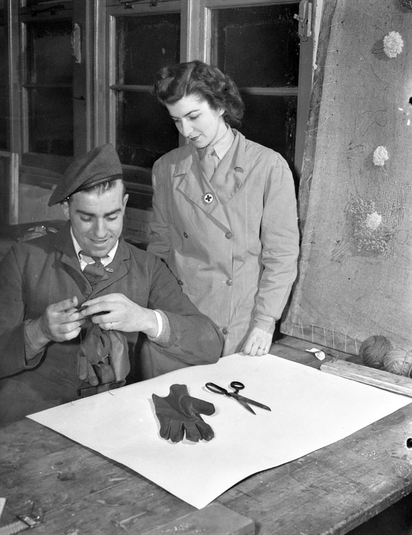 Handicrafts Officer Mrs. Guy Savard of the Canadian Red Cross instructing Private E.L. Woods in glovemaking at No.18 Canadian General Hospital, Royal Canadian Army Medical Corps (R.C.A.M.C.), Colchester, England, 15 December 1944.