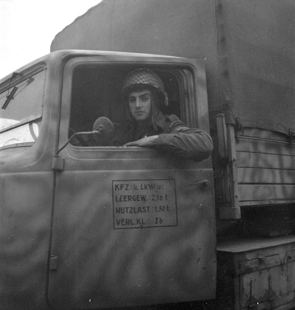 Private V.P. Blough of The Cameron Highlanders of Ottawa (M.G.) evacuating civilians in a captured German truck, Calais, France, 29 September 1944.