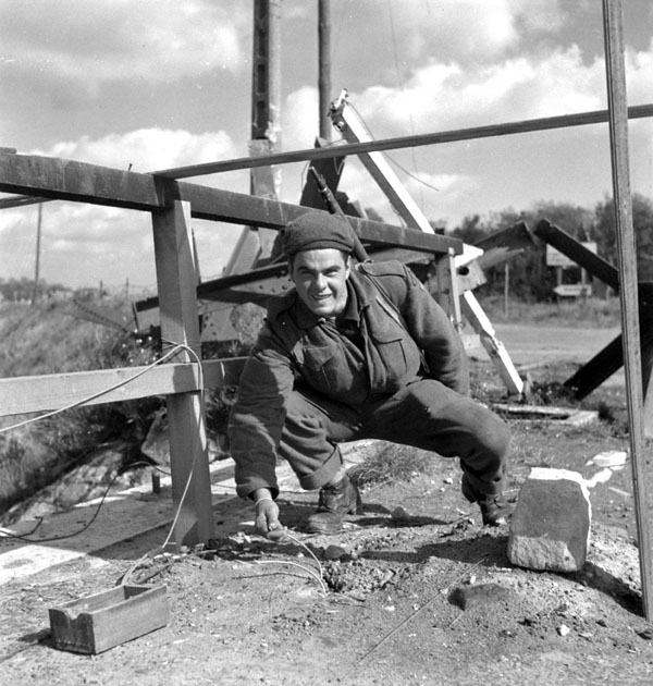 Rifleman N.R. Menard of The Queen's Own Rifles of Canada dispalying detonators clipped to the demolition charges on a bridge, Calais, France, 1 October 1944.