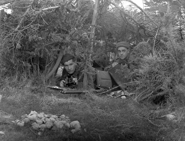 Privates H. Drake and J.R. Dean of the 48th Highlanders of Canada in a camouflaged observation post during manoeuvres, England, ca. 1941.