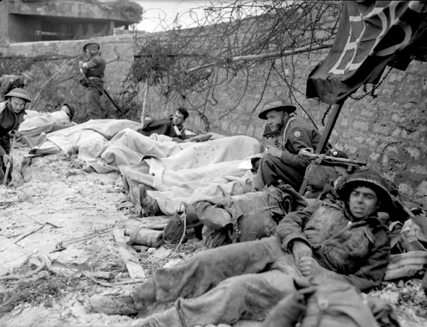 Wounded Canadian soldiers awaiting evacuation to a Casualty Clearing Station of the Royal Canadian Army Medical Corps (R.C.A.M.C.) in the Normandy beachhead, France, 6 June 1944.