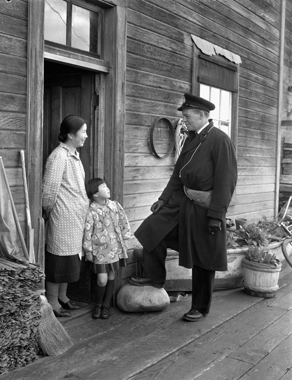 An unidentified officer of the Royal Canadian Naval Volunteer Reserve (R.C.N.V.R.) talking with a Japanese-Canadian family during the internment of fishing boats, British Columbia, Canada, 10 December 1941.