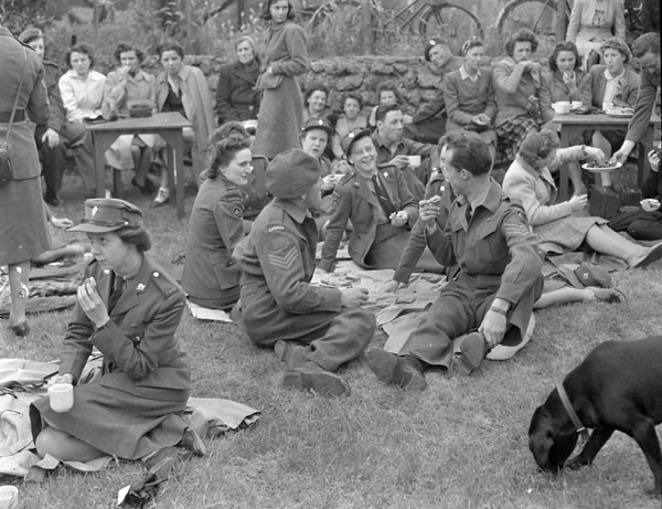 Personnel of Canadian Military Headquarters having lunch at Hampton Court during a boat trip on the Thames River, England, 16 June 1945.