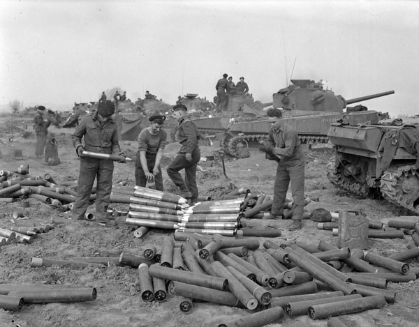 Personnel of The Canadian Grenadier Guards stacking 75mm. shells near the regiment's positioned Sherman tanks south of Emmerich, Germany, 28 March 1945.