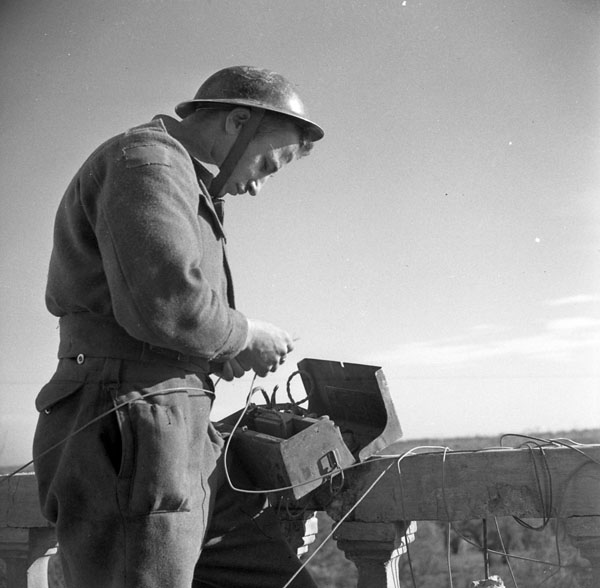 Gunner R.G. Marquis of the Royal Canadian Artillery (R.C.A.) testing a telephone line near San Tommaso, Italy, 25 January 1944.