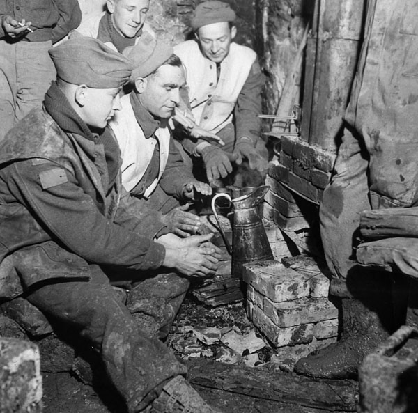 Gunners of the 2nd Field Regiment, Royal Canadian Artillery (R.C.A.), warming up around a fireplace in a damaged farmhouse, Italy, 15 February 1944.