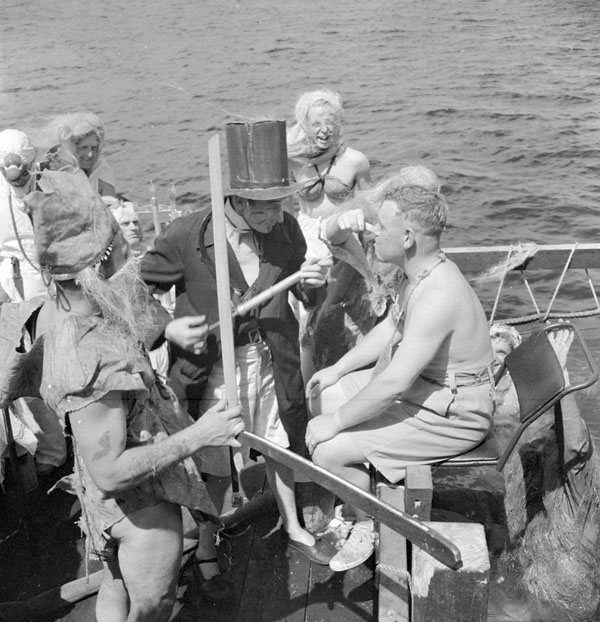 Commander Hugh F. Pullen being prepared for initiation into the court of King Neptune aboard H.M.C.S. UGANDA at sea, 7 March 1945.