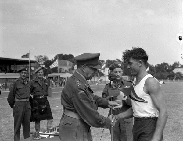 General H.D.G. Crerar presenting an award to Trooper H. Kempa at the 1st Canadian Army Sports Meet, Hilversum, Netherlands, 20 June 1945.