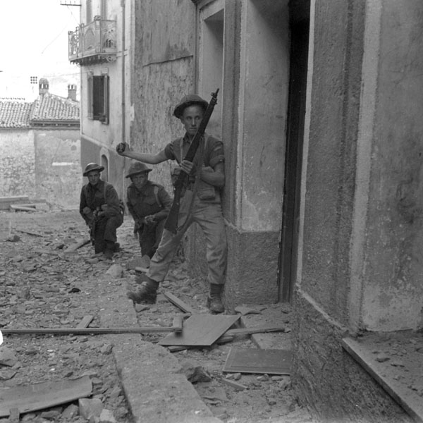 Infantrymen of The Carleton and York Regiment preparing to lob a hand grenade into a sniper's hideout, Campochiaro, Italy, 23 October 1943.