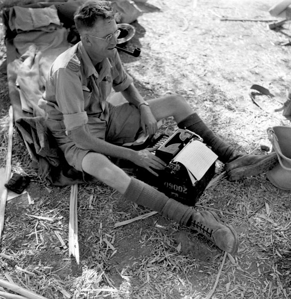War correspondent Ross Munro of the Canadian Press typing a story in the battle area between Valguarnera and Leonforte, Italy, August 1943.