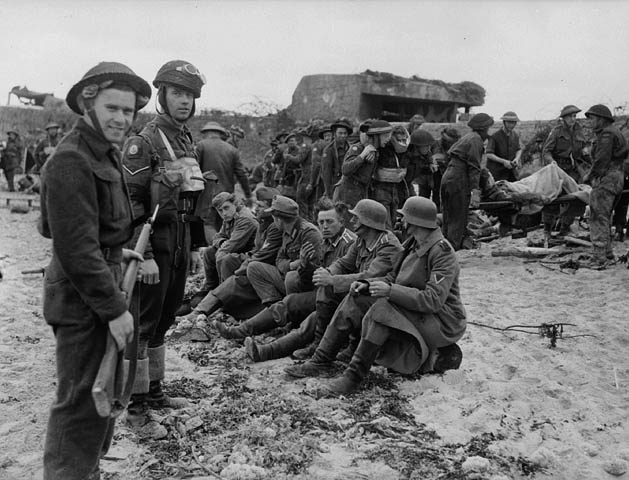 A member of the Canadian Provost Corps (C.P.C.) guarding the first German prisoners to be captured by Canadian soldiers in the Normandy beachhead, France, 6 June 1944.