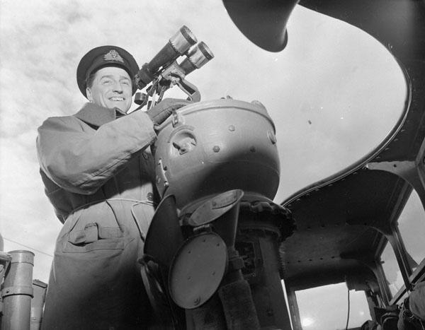 Lieutenant-Commander Desmond W. Piers, Commanding Officer, on the bridge of the destroyer H.M.C.S. RESTIGOUCHE, which is escorting Convoy SC-107 at sea, 21 April 1944.